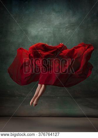 Heart Beating. Graceful Classic Ballerina Dancing On Dark Studio Background. Deep Red Cloth. The Gra