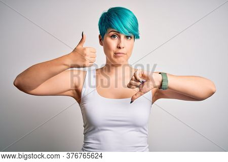 Young beautiful woman with blue fashion hair wearing casual t-shirt over white background Doing thumbs up and down, disagreement and agreement expression. Crazy conflict