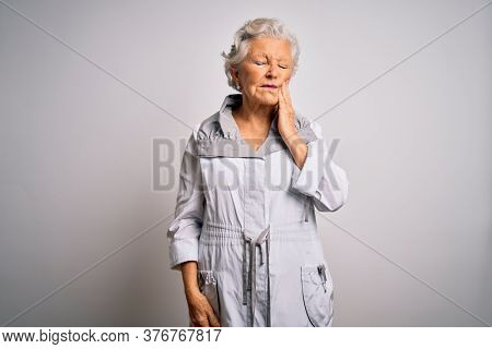 Senior beautiful grey-haired woman wearing casual jacket standing over white background touching mouth with hand with painful expression because of toothache or dental illness on teeth. Dentist