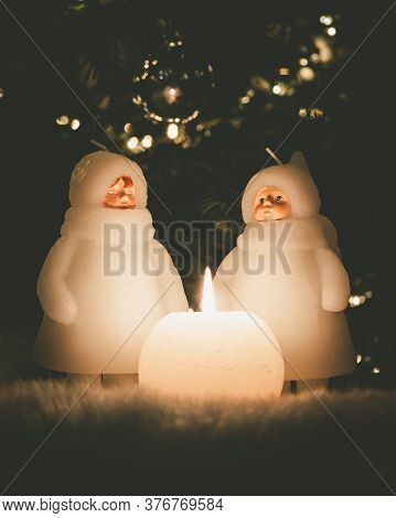 Christmas Child Candle Dolls Stand In Front Of A Christmas Tree, There Is A Burning Round Candle In