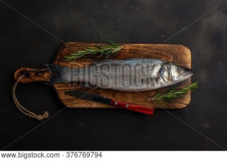 Fresh Seabass Fish With Rosemary And Knife On Black Table. Seafood Concept.