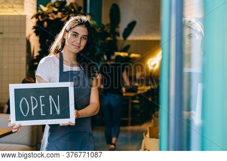 Portrait Of A Female Waitress In Apron Showing Chalkboard With Open Sign At The Coffee Shop. Local B