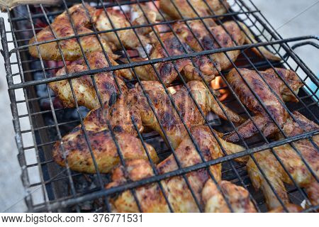 The Process Of Cooking Outdoors. Cooking At The Stake. Chicken Wings Are Cooked On The Grill At The