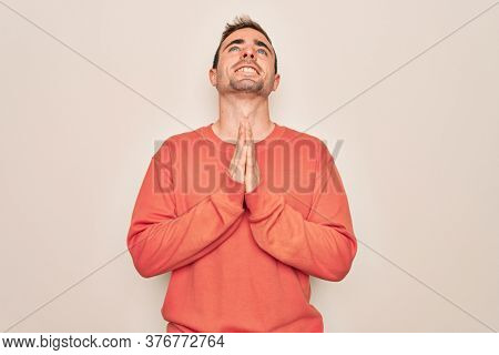 Young handsome man with blue eyes wearing casual sweater standing over white background begging and praying with hands together with hope expression on face very emotional and worried. Begging.