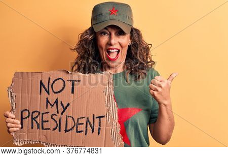Middle age brunette communist woman holding banner with not my president message pointing thumb up to the side smiling happy with open mouth