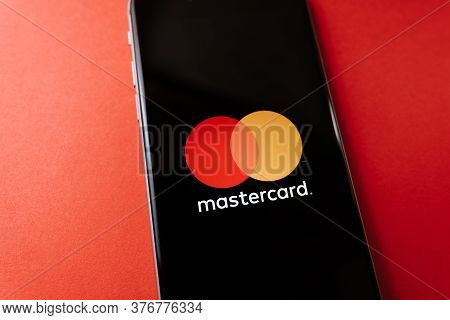Mastercard Logo On The Smartphone Screen, On Red Background. High Quality Photo