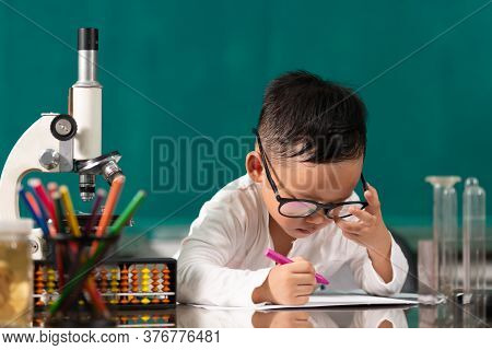 Cute Child Asian Boy Doing Homework. Clever Kid Drawing At Desk. Schoolboy. Elementary School Studen