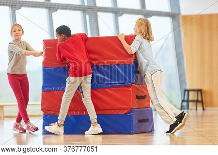 Pupils in physical education in the gym of elementary school with jumping box