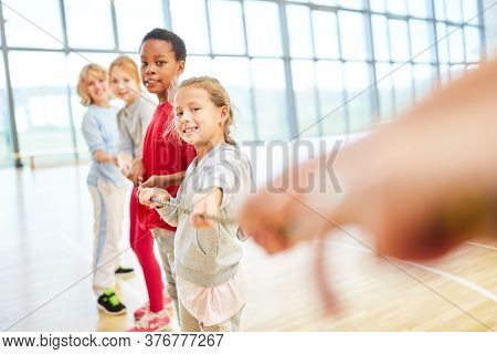 Group of children at tug of war in physical education in elementary school