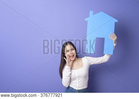 Portrait Of Beautiful Woman  Is Holding Blue  Home On Purple Background