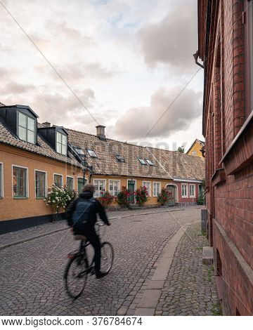 A University Student Runs His Bike Along The Small Cobblestoned Streets Bordered With Colorful House