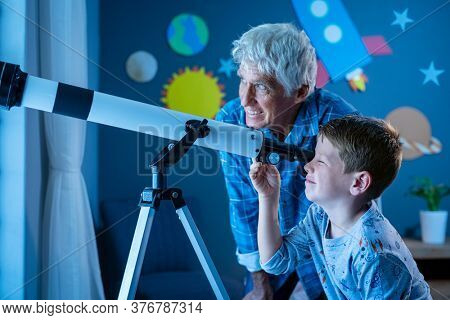 Grandfather teaching grandson using telescope to see planets and galaxy. Child watching stars through a telescope at night with senior man. Grandpa and grandchild looking together at positive future.