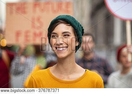 Smiling latin woman in march to protest on equality rights. Happy young woman empowerment strike on street looking away. Portrait of confident casual girl in march fighting for freedom.