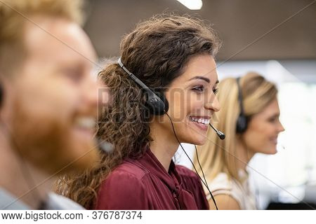 Smiling woman call center operator with headset working on computer. Positive smiling agents in conversation with customer over headset, sitting in row. Consulting and assistance helpdesk service.