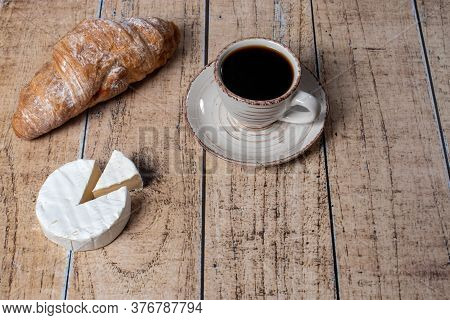 A Cup Of Coffee, Camembert Cheese And A Croissant. Idea For A Delicious Breakfast.