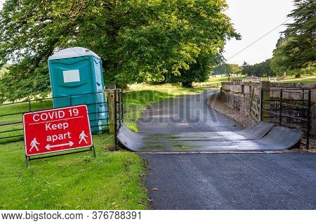 A Covid-19 Social Distancing Warning Sign And A Plastic Portable Toilet Next To A Cattle Grid On A P