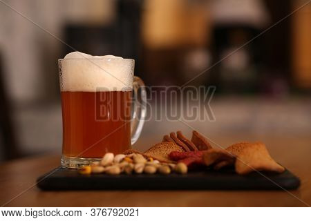 Pint Of Cold Tasty Beer Served With Snacks On Table
