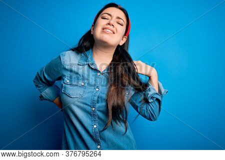 Young brunette woman wearing casual denim shirt over blue isolated background Suffering of neck ache injury, touching neck with hand, muscular pain