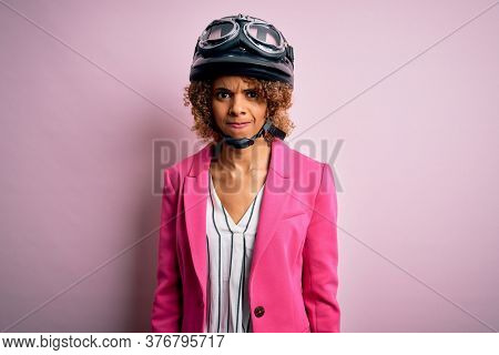 African american motorcyclist woman with curly hair wearing moto helmet over pink background skeptic and nervous, frowning upset because of problem. Negative person.