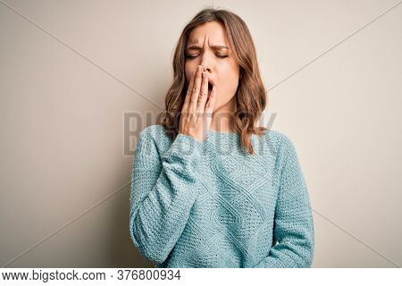Young blonde woman wearing casual blue winter sweater over isolated background bored yawning tired covering mouth with hand. Restless and sleepiness.