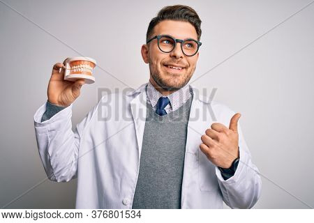 Young dentist man with blue eyes holding orthodontic dental prosthesis over isolated background pointing and showing with thumb up to the side with happy face smiling