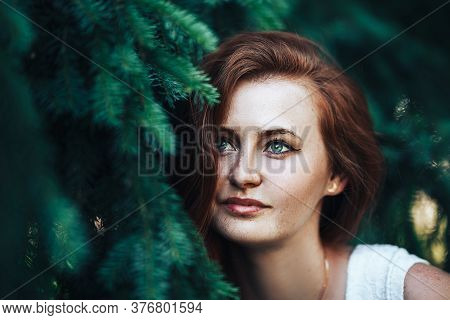 Young Beautiful Girl With Red Hair And With Freckles On Her Face, Red-haired Girl On A Background Of