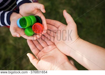 Baby Puts Plastic Lids In Mother's Hands. Parent And His Child Collect Cover. Recyclable. Collecting