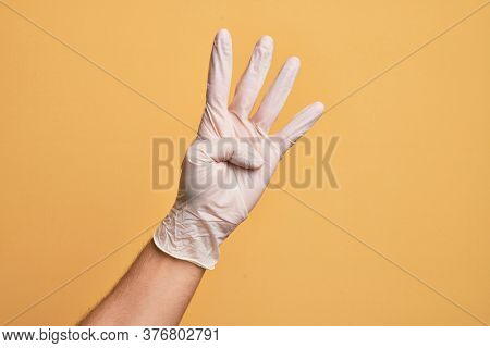 Hand of caucasian young man with medical glove over isolated yellow background counting number 4 showing four fingers