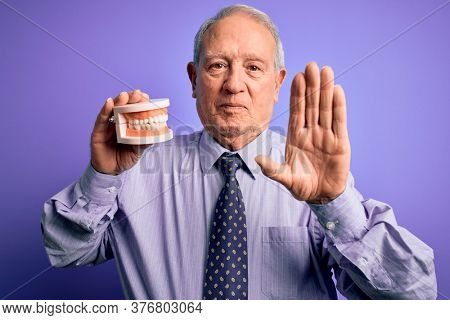 Grey haired senior man holding orthodontic prosthesis denture over purple background with open hand doing stop sign with serious and confident expression, defense gesture