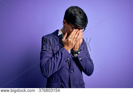 Young handsome business man wearing jacket and glasses over isolated purple background rubbing eyes for fatigue and headache, sleepy and tired expression. Vision problem