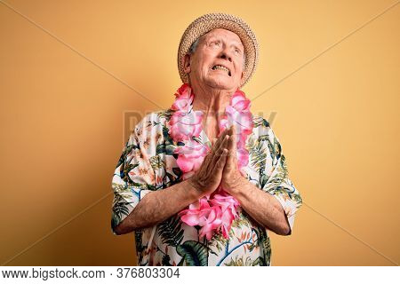 Grey haired senior man wearing summer hat and hawaiian lei over yellow background begging and praying with hands together with hope expression on face very emotional and worried. Begging.