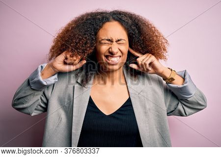 Young african american businesswoman with afro hair wearing elegant jacket covering ears with fingers with annoyed expression for the noise of loud music. Deaf concept.