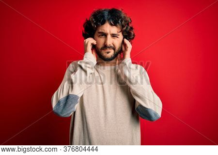 Young handsome man with beard wearing casual sweater standing over red background covering ears with fingers with annoyed expression for the noise of loud music. Deaf concept.