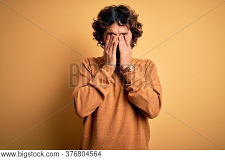 Young handsome man with beard wearing casual sweater standing over yellow background rubbing eyes for fatigue and headache, sleepy and tired expression. Vision problem