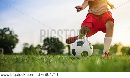 Boy Kicking A Ball While Playing Street Soccer Football On The Green Grass Field For Exercise. Outdo