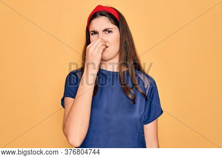 Young beautiful brunette woman wearing red lips over yellow background smelling something stinky and disgusting, intolerable smell, holding breath with fingers on nose. Bad smell