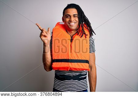 Young african american afro man with dreadlocks wearing orange lifejacket with a big smile on face, pointing with hand and finger to the side looking at the camera.