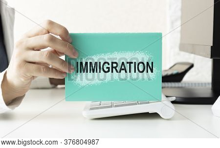 An Immigration Worker Holds A Notepad That Says Immigration.