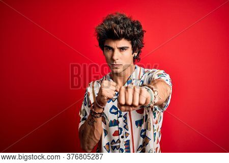 Young handsome man on vacation wearing summer shirt over isolated red background Punching fist to fight, aggressive and angry attack, threat and violence