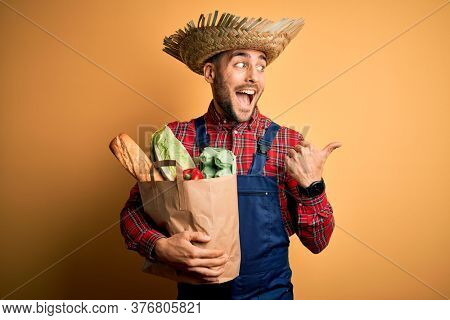 Young rural farmer man holding fresh groceries from marketplace over yellow background pointing and showing with thumb up to the side with happy face smiling