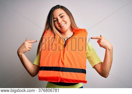 Young beautiful blonde woman with blue eyes wearing orange lifejacket over white background looking confident with smile on face, pointing oneself with fingers proud and happy.