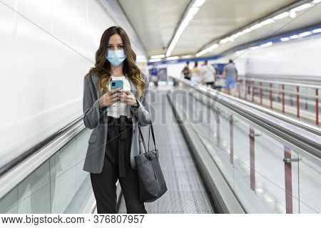 Young Businesswoman With A Face Mask Walking With Her Smartphone In Her Hand Through The Subway Corr