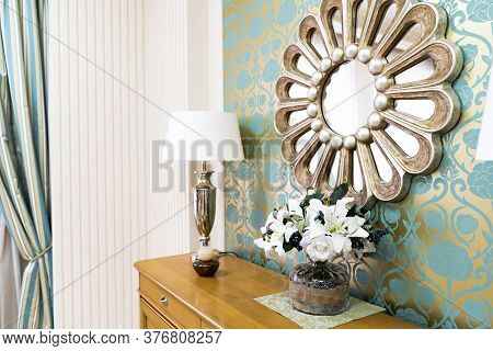Stylish Vintage Style Home Interior With Wooden Commode And Decorated Round Mirror. Symmetrical Read