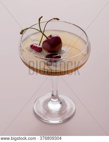 Sparkling Cocktail With Sweet Cherry On Pink Background. Concept Of Sparkling Beverages With Garnish