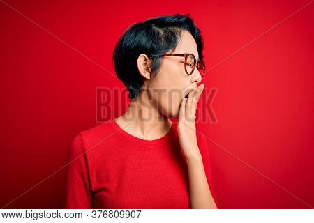 Young beautiful asian girl wearing casual t-shirt and glasses over isolated red background bored yawning tired covering mouth with hand. Restless and sleepiness.