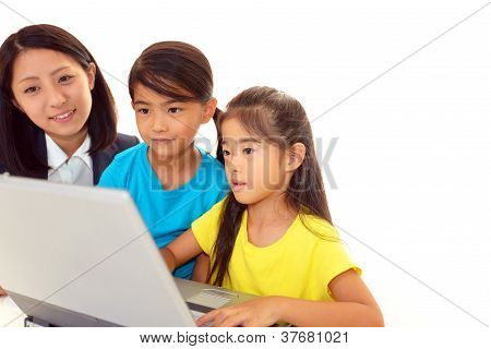 Smiling girls using a laptop