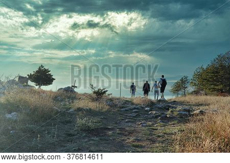 Four Friends Hiking Together, Reach The Top Of A Small Hill, Stone Path Overgrown With Grass Leading