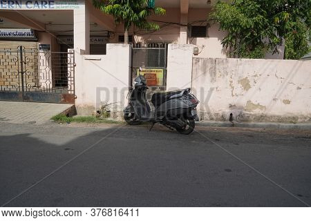An Old Gray Colored Tvs Jupiter Scooter Parked Outside A House. Two-wheeler Is Parked At Road Side I