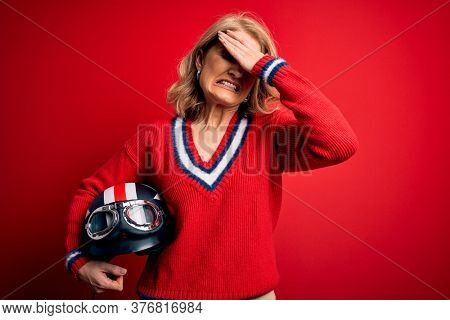 Middle age beautiful blonde motorcyclist woman holding moto helmet over red background stressed with hand on head, shocked with shame and surprise face, angry and frustrated. Fear and upset.