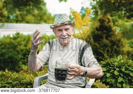 Portrait Of A Handsome Elderly Man Of 87 Years Old, Drinking A Cool Drink In The Garden After Work.